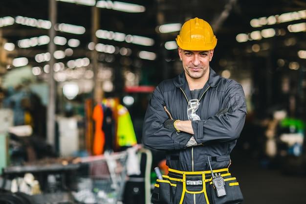 Gelukkige arbeider, wapens van de portret de knappe arbeid die met de riem van de veiligheidspakhulpmiddelen wordt gevouwen en de radiodienstmens in fabriek.