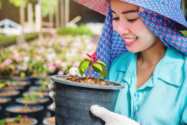 Gelukkige arbeiders aziatische vrouw met het planten van bloemen die bloemen in serre behandelen.
