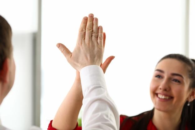 Gelukkige arbeiders die in bureau nieuwe collectieve verwezenlijking vieren door gezamenlijke hoogte vijf in luchtclose-up te geven