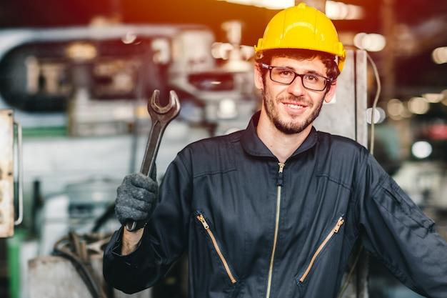 Gelukkige arbeiders nerdy glazen die in de hand van de de industriefabriek werken met het veiligheidspak en de helm van de moersleutelslijtage.