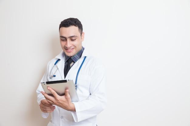 Gelukkige arts die digitale tablet gebruiken bij kliniek