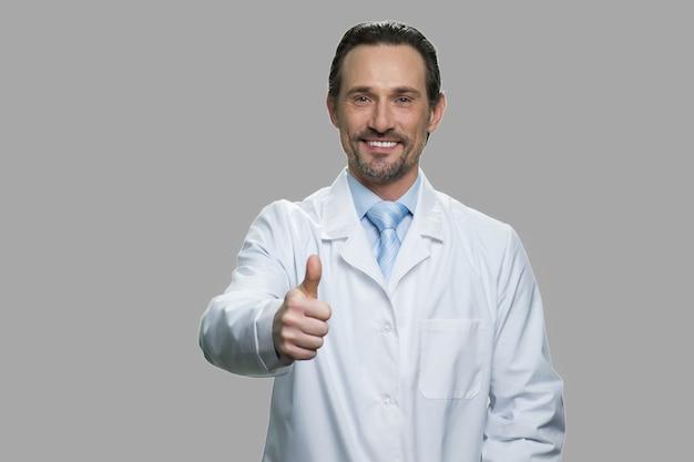 Gelukkige arts of wetenschapper die duim toont ondertekent omhoog. man van middelbare leeftijd in witte jas duim opgevend gebaar tegen grijze achtergrond. goed werkconcept.