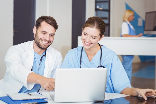 Gelukkige artsen die laptop met behulp van terwijl het bespreken bij bureau