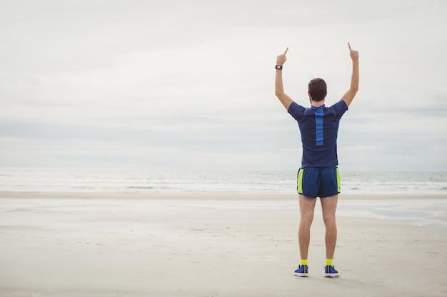 Gelukkige atleet die zich op het strand met zijn opgeheven handen bevindt