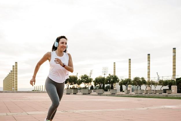 Gelukkige atletische vrouw die rent terwijl ze naar muziek luistert buiten in de stad