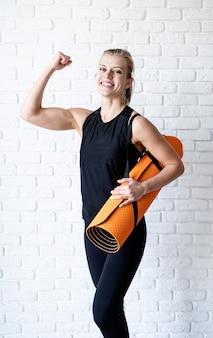 Gelukkige atletische vrouw in zwarte sportwear die haar biceps op witte bakstenen muurachtergrond toont