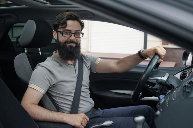Gelukkige autobestuurder met vastgemaakte veiligheidsgordel