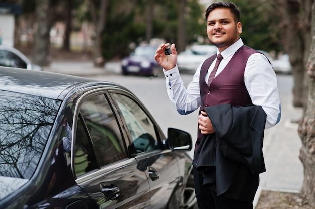 Gelukkige autobezitter met dichtbije sleutels. modieuze indische zakenman in formele slijtage die zich tegen zwarte bedrijfsauto op straat van stad bevinden.