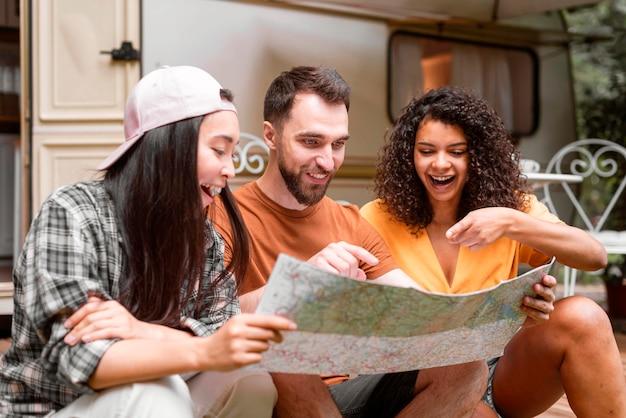 Gelukkige avontuurlijke vrienden die op een kaart wijzen