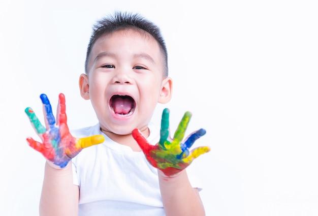 Gelukkige aziaat toont weinig babyjongen hand hij waterkleur of vingerverf op handen op wit heeft