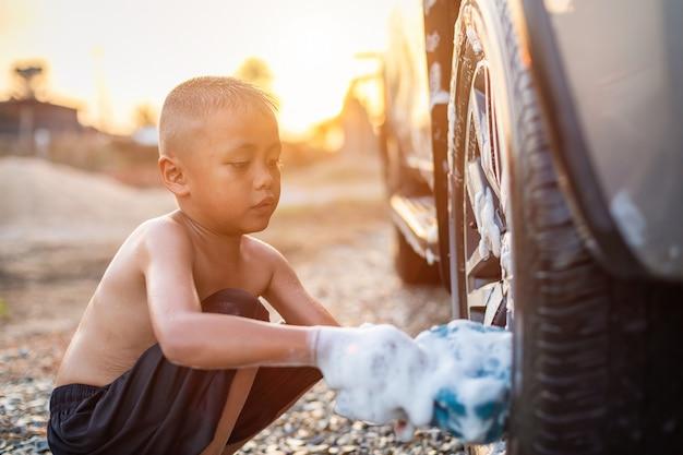 Gelukkige aziaat weinig jongen met witte zeep en het gebruiken van blauwe spons aan het wassen van de auto bij openlucht in zonsondergangtijd
