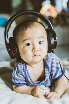 Gelukkige aziatische baby die van muziek geniet die grote zwarte hoofdtelefoons met behulp van.