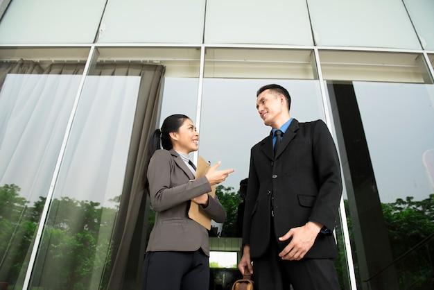 Gelukkige aziatische bedrijfsmensen die over zaken spreken