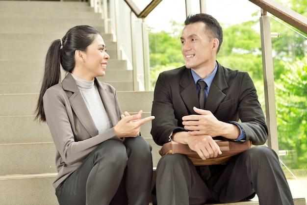 Gelukkige aziatische bedrijfsmensen in toevallige gesprekken