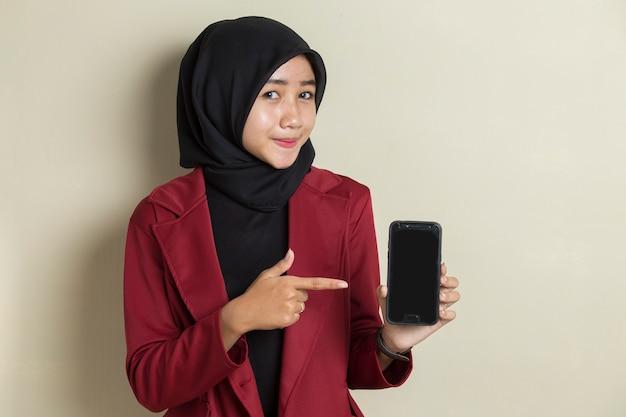 Gelukkige aziatische bedrijfsvrouw in hijab die mobiele celtelefoon aantoont. portret van glimlachende vrouw, die zich voordeed