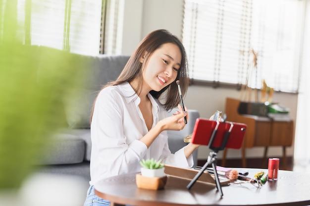 Gelukkige aziatische bloggervrouw die videomake-upschoonheidsmiddel thuis opnemen