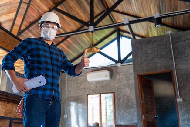 Gelukkige aziatische bouwingenieur inspecteert de houtstructuur onder het dak op de bouwplaats of de bouwplaats van een huis.