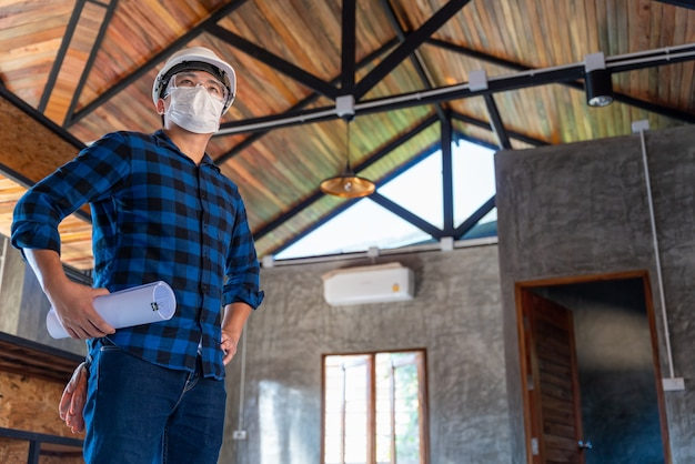 Gelukkige aziatische bouwingenieur-technicus na inspectie van de houtstructuur onder het dak op de bouwplaats of bouwplaats van een huis.