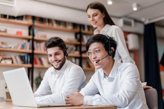 Gelukkige aziatische call centreexploitant die met hoofdtelefoon in het bureau glimlachen