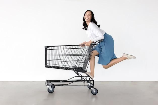 Gelukkige aziatische dame in het winkelen actie met boodschappenwagentje