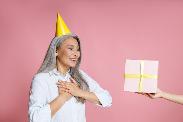 Gelukkige aziatische dame van middelbare leeftijd met lang grijs haar en gele feestmuts kijkt naar de geschenkdoos op de hand van een vriend op een roze achtergrond in de studio