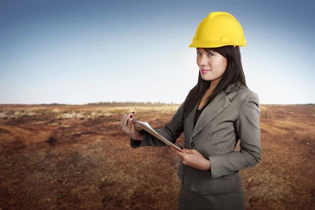 Gelukkige aziatische de holdingsblauwdruk van de contractantsvrouw op klembord