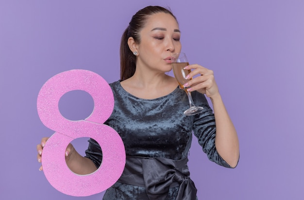 Gelukkige aziatische die nummer acht van de vrouwenholding van karton en glas champagne houdt die vierende internationale vrouwendag vieren die zich over purpere muur bevinden