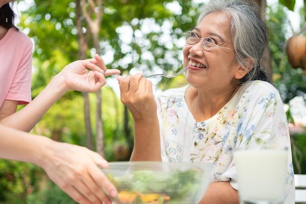 Gelukkige aziatische dochter luncht met haar familie en voert salade aan moeder in de achtertuin.