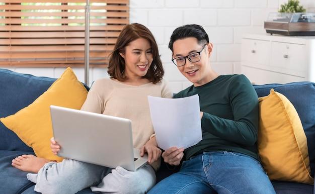 Gelukkige aziatische echtgenoot die de rekeningen van nutsbedrijven analyseert die thuis samen zitten.