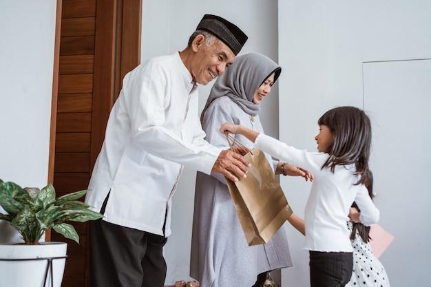Gelukkige aziatische familie die cadeau geeft aan hun moslimgrootouders tijdens de viering van eid mubarak. verrassingsgeschenk voor familie