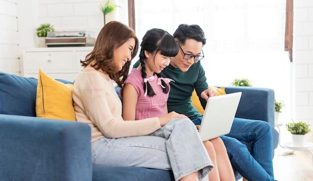 Gelukkige aziatische familie die computerlaptop samen op bank thuis met behulp van woonkamer.