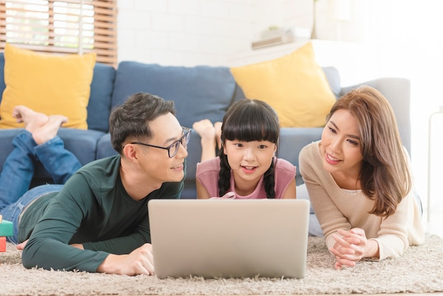 Gelukkige aziatische familie die computerlaptop samen op bank thuis woonkamer met behulp van.