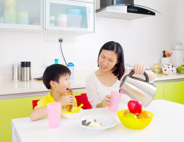 Gelukkige aziatische familie die ontbijt in de keuken heeft