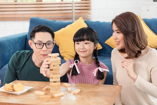 Gelukkige aziatische familie die plezier heeft met het spelen van blokspel in de woonkamer thuis.