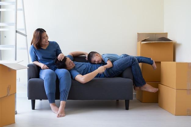 Gelukkige aziatische familie die pret hebben tijdens het verplaatsen van dag en bij nieuw huis verhuizen. verhuizen en nieuw onroerend goed concept