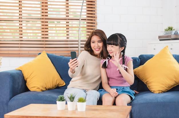 Gelukkige aziatische familie die smartphone gebruikt die samen een selfie-foto maakt op de bank in de woonkamer