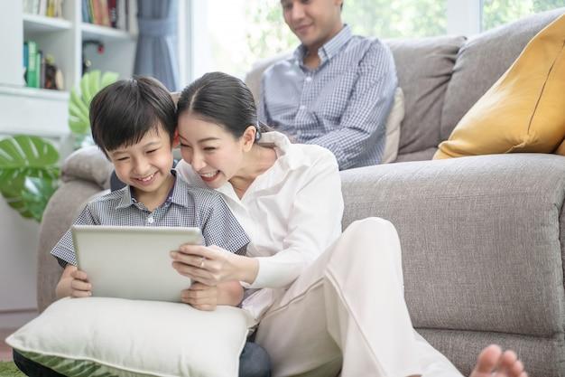 Gelukkige aziatische familie het besteden tijd samen aan bank in woonkamer.