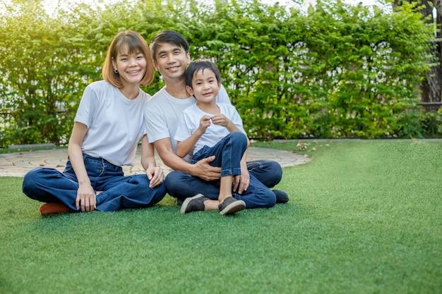 Gelukkige aziatische familie in de achtertuin op het gras