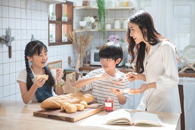 Gelukkige aziatische familie in de keuken. moeder en zoon en dochter en kinderen verspreiden aardbeienyam op brood, vrijetijdsactiviteiten thuis.