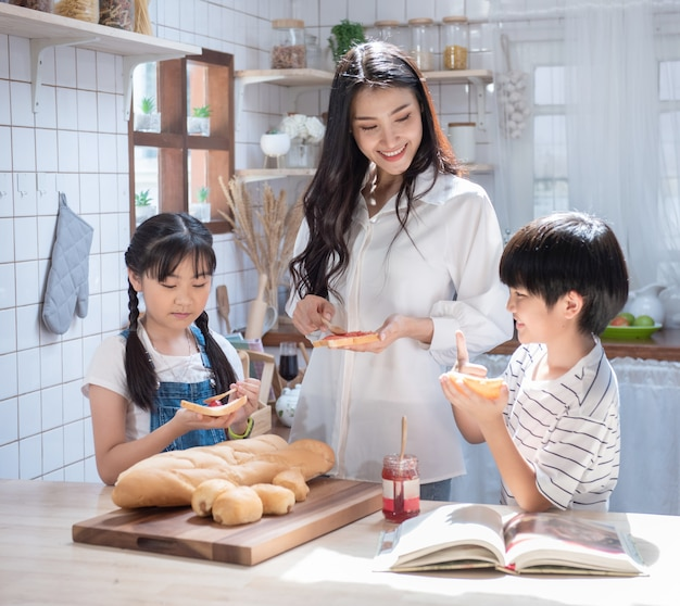 Gelukkige aziatische familie in de keuken. moeder en zoon en dochter verspreidden aardbeienjam op brood, vrijetijdsactiviteiten thuis.