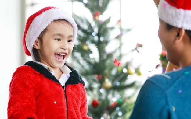 Gelukkige aziatische familie kleine schattige dochter draagt een trui met een rode en witte kerstmuts die staat te lachen, opwindend als vader trekt exploderende feestpopper glanzend papier confetti viert kerstmis.