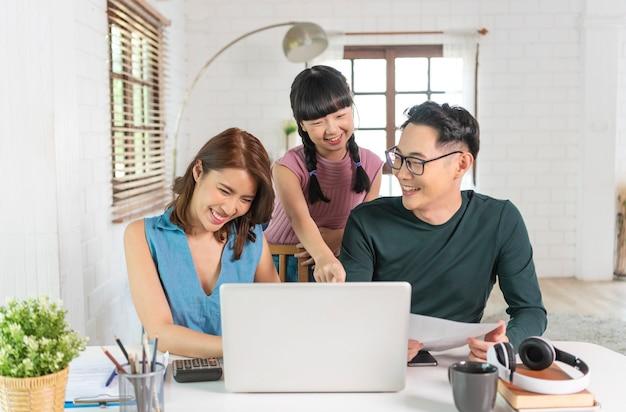 Gelukkige aziatische familie met behulp van computer laptop samen op desktop op kantoor aan huis.
