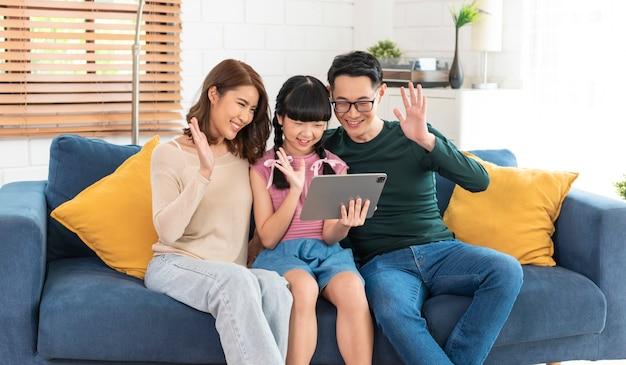 Gelukkige aziatische familie met behulp van tablet video-oproep virtuele vergadering samen op de bank thuis woonkamer.