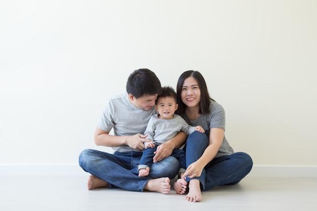 Gelukkige aziatische familie met één babyjongen die pret samen op vloer heeft
