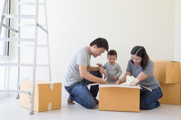 Gelukkige aziatische familie met kartondozen in nieuw huis bij het bewegen van onroerende goederen dag, en huisconcept