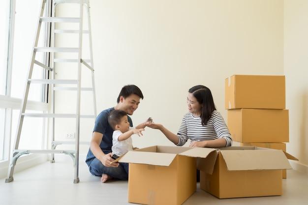 Gelukkige aziatische familie met kartonnen dozen in nieuw huis op bewegende dag