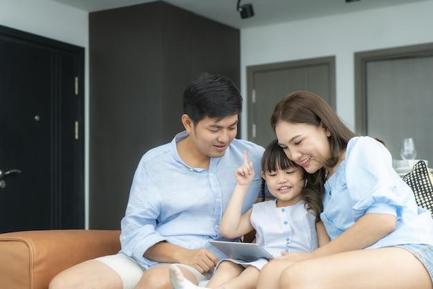 Gelukkige aziatische familie met vader, moeder en dochter die op bank zitten en digitale tablet gebruiken
