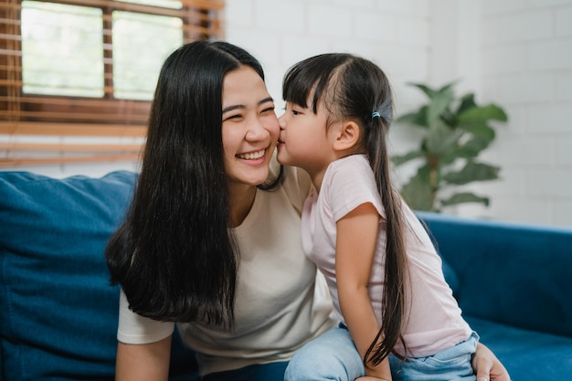 Gelukkige aziatische familie moeder en dochter omarmen zoenen op wang feliciteren met verjaardag thuis.