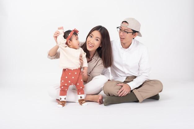 Gelukkige aziatische familie op witte muur