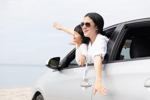Gelukkige aziatische familie op zomervakantie moeder en dochter open armen spelen vliegtuig samen vliegen in de auto op het strand. vakantie en auto reizen concept.